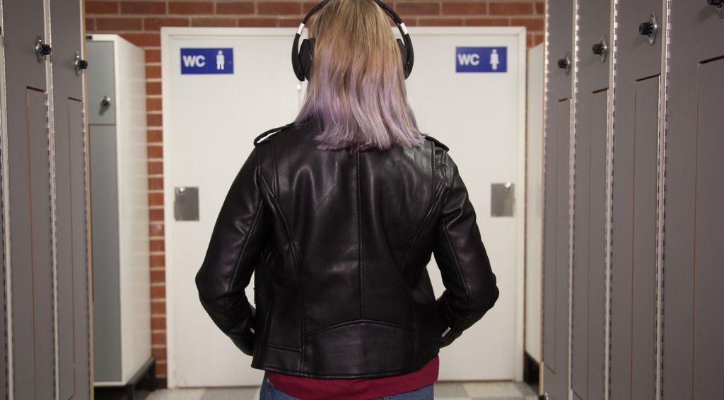 Nuori henkilö katsoo koulussa selin kahta wc-koppia, joissa on toisessa nais- ja toisessa miessymbolit.