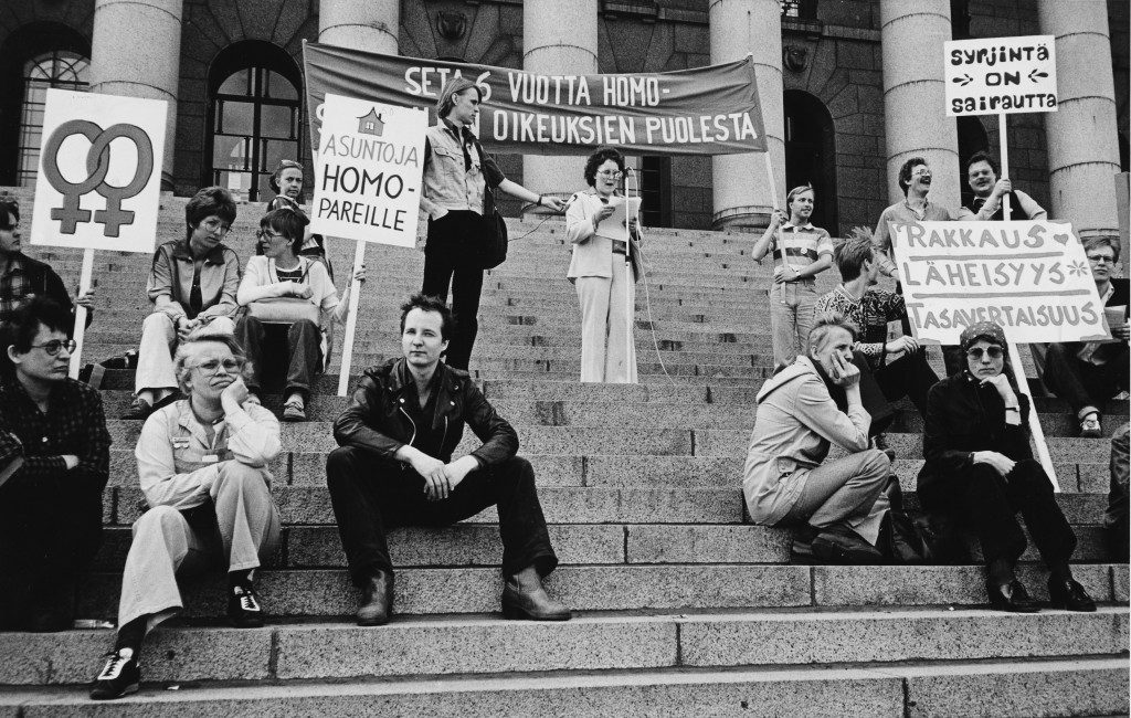 Kuvassa on vuoden 1980 Vapaustuspäivien mielenosoitus eduskuntatalon portailla. Kuvassa on useita ihmisiä kyltteineen. Katse kiinnittyy täysin tummissa istuvaan nuoreen mieheen, joka katsoo avoimesti kameraan.