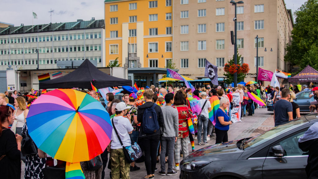 Kuvassa on ihmisiä järjestäytymässä Lahti priden -kulkueeseen. Etualalla avoinna sateenvarjo sateenkaaren väreissä. Kuvaaja Joni Niuranen.