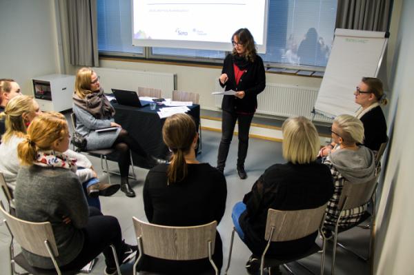 Kuvassa on Setan koulutussuunnittelija Marita Karvinen opettamassa tuoleilla istuvia ihmisiä.