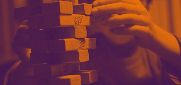 Kuvassa lapsi pelaa puupalikoista koostuvaa peliä huojuvaa tornia.