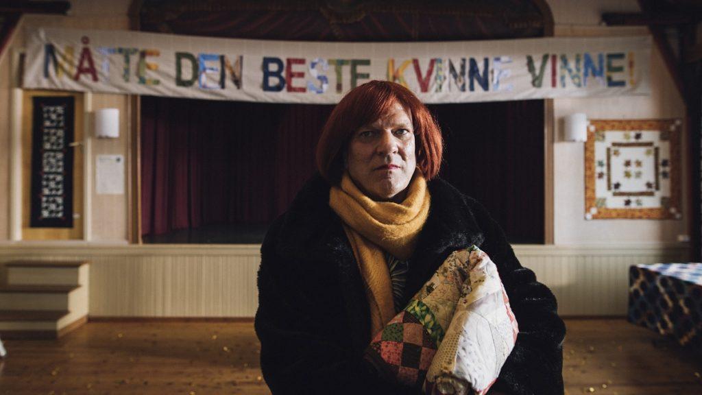 kuvassa on transvestiitti juhlasalissa huopa sylissään