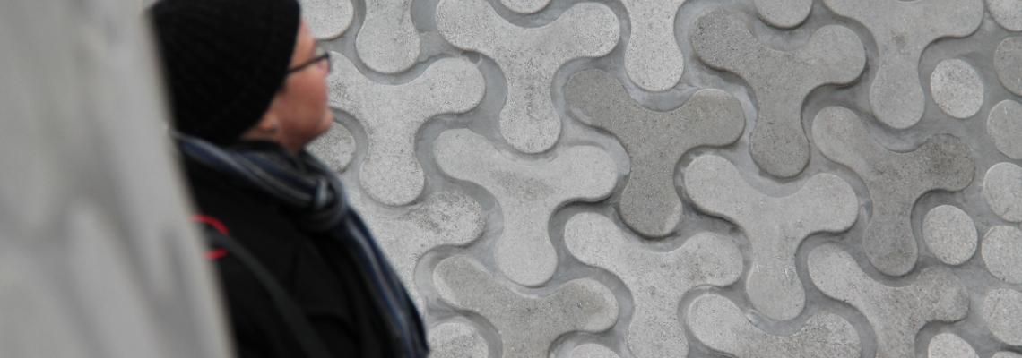 Kuvassa ihminen nojaa betoniseen teokseen eikä häntä näy kunnolla.