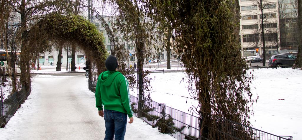 Kuvassa ihminen seisoo puukaaren alla.