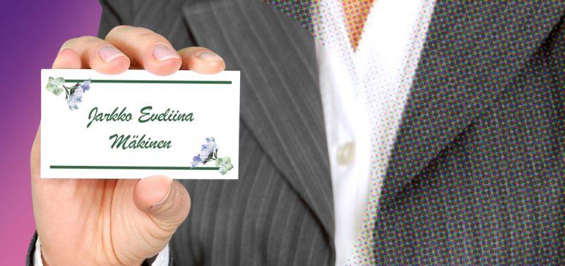 Kuvassa on puvuntakissa ja kauluspaidassa olevan henkilön rintakuva. Hän pitelee käyntikorttia, jossa lukeaa Jarkko Eveliina Mäkinen.