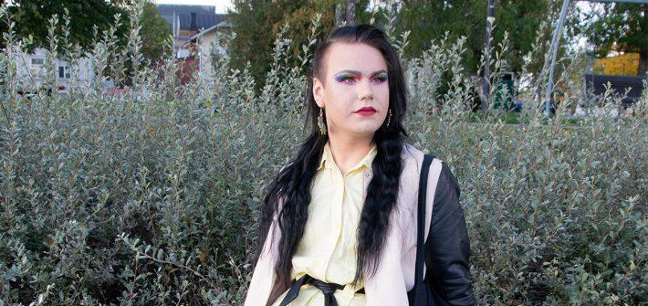 Kuvassa on oikealle katsova Seve Hujanen, jolla on pitkä musta tukka, vahva meikki ja kesäiset vaatteet.
