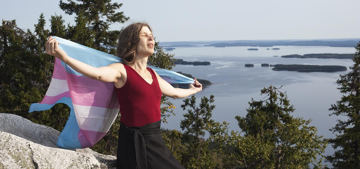Kuvassa on Alia Dannenberg pitelemässä translippua selkänsä takana aurinkoa kohti. Taustalla on uljas järvimaisena.