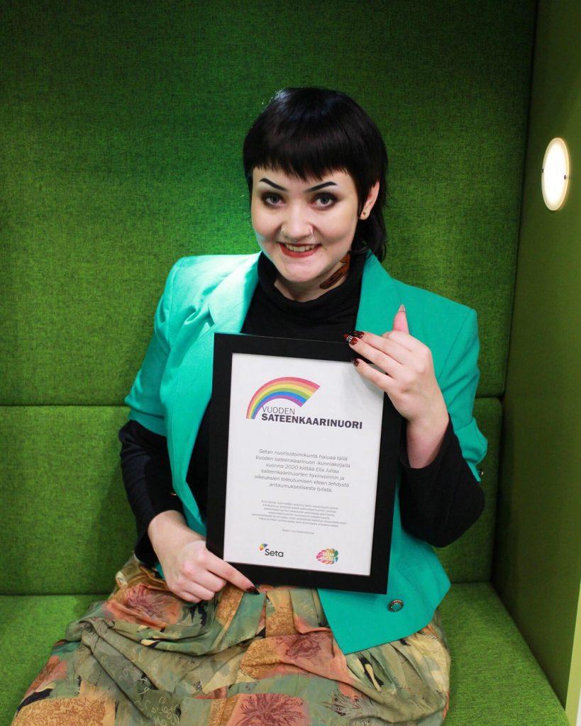 Vuoden sateenkaarinuori Ella Julia pitää palkintodioplomia sylissä. Hänellä on musta tukka ja pullonvihreä takki
