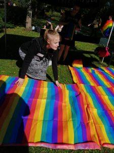 Etsivä nuorisotyöntekijä Sanni Laurila asettelee Pride-juhlassa vilttejä sateenkaarinuorten nurmikaistaleelle.