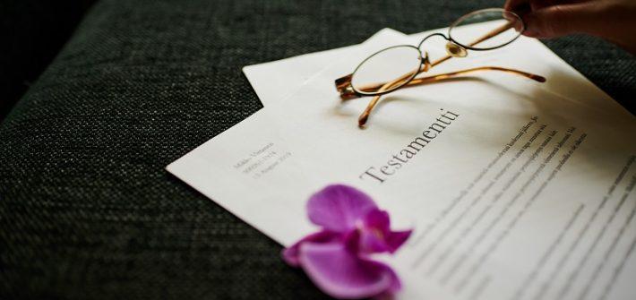 Kuvassa on testamentti, jonka päällä on orkidean kukka ja käsi pitelemässä kultasankaisia silmälaseja