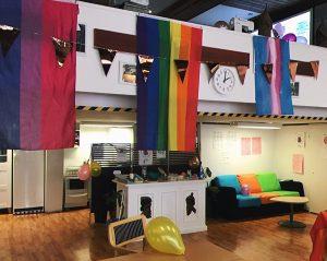 Kuvassa on nuorisotila, jossa alakerrassa sohva ja tiski, joiden yläpuolella roikkuu sateenkaarilippu, translippu ja biseksuaalisuuden lippu.