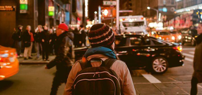 Kuvassa on pipopäinen isompi lapsi, joka kulkee reppu selässä illalla keskellä tiheästi liikennöityä kaupunkia.