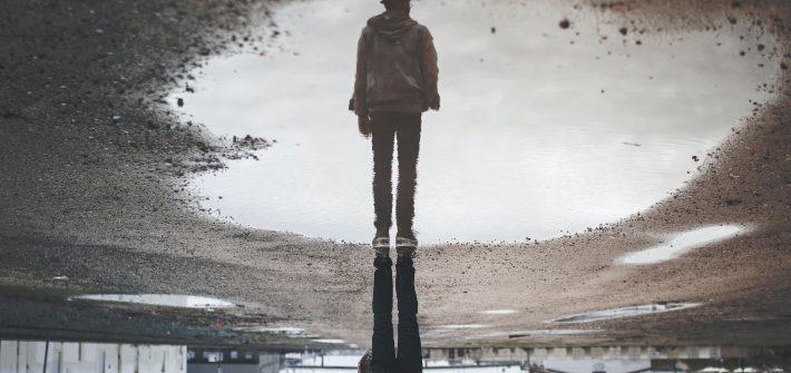 Kuvassa on lätäkössä heijastus seisovasta ihmisestä.